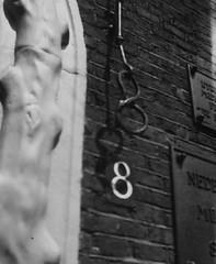 """<p>De deurbel in de vorm van een krakeling. Het pand heeft nogal wat verschillende huisnummers gehad. Een bord bij de ingang geeft een citaat uit 1668 van Everard Meijster: """"Uterech; .... zij is de parel van Euroop,"""" Coll. Het Utrechts Archief.</p>"""