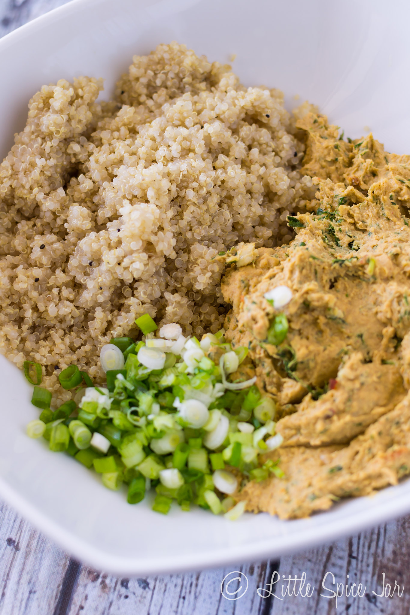 quinoa, falafel mixture and chopped scallions in white dish