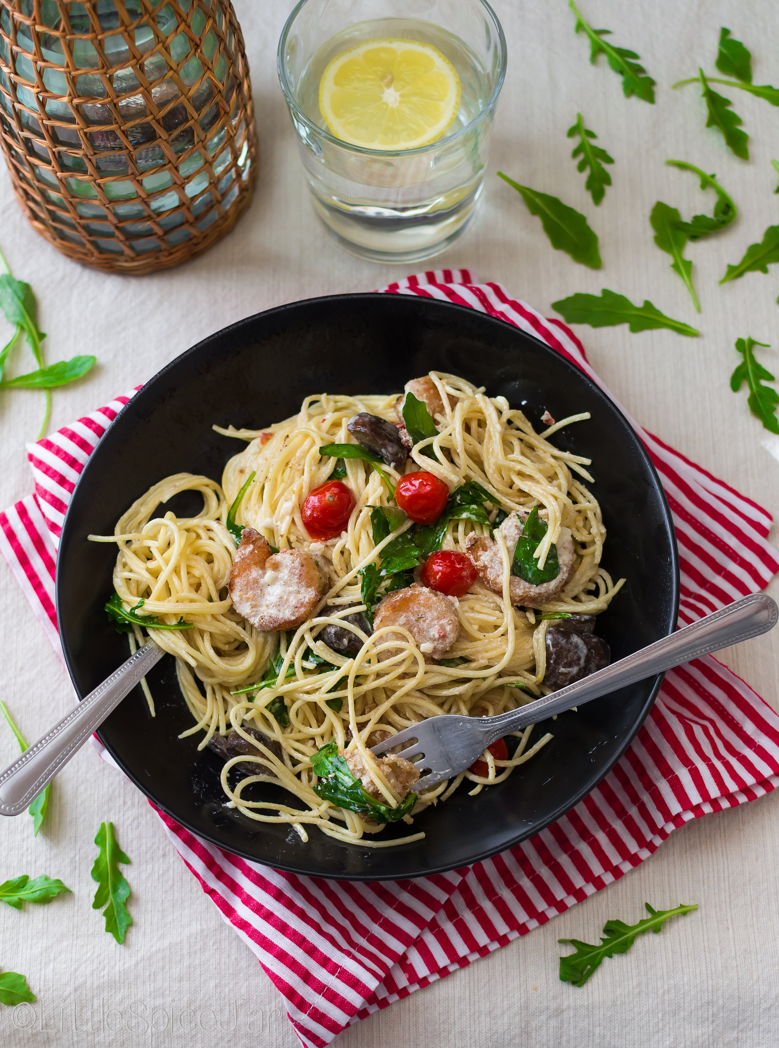 food scene with pasta topped with tomatoes mushroom and shrimp