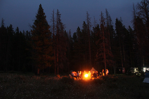"A group of students sit around the campfire talking with their escorts during a trip into the Bob Marshall and Scapegoat Wilderness Areas. Their adventure on horseback and by foot is documented in the U.S. Forest Service video ""Untrammeled."" (U.S. Forest Service)"