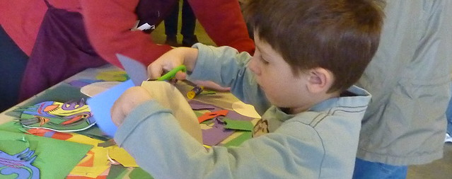 young boy using scissors to cut colored construction paper