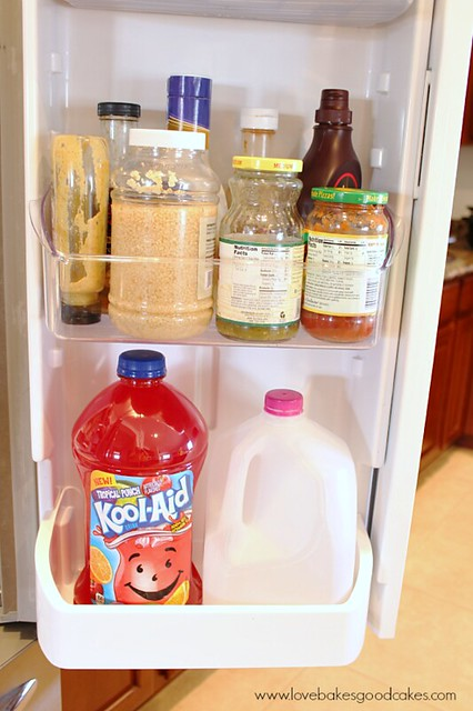 Refrigerator door shelf with Kool Aid bottle of flavored drink.