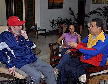 Former Cuban President Fidel Castro visits Venezuelan President Hugo Chavez while he is recuperating from surgery in Cuba. The woman sitting between them is unidentified. by Pan-African News Wire File Photos