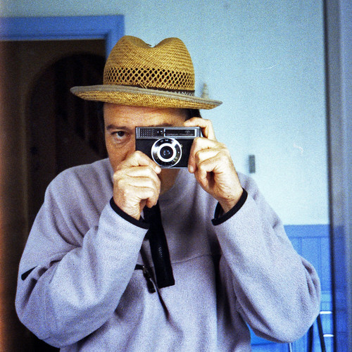 reflected self-portrait with Agfa Isomat-Rapid camera and back to front straw hat by pho-Tony