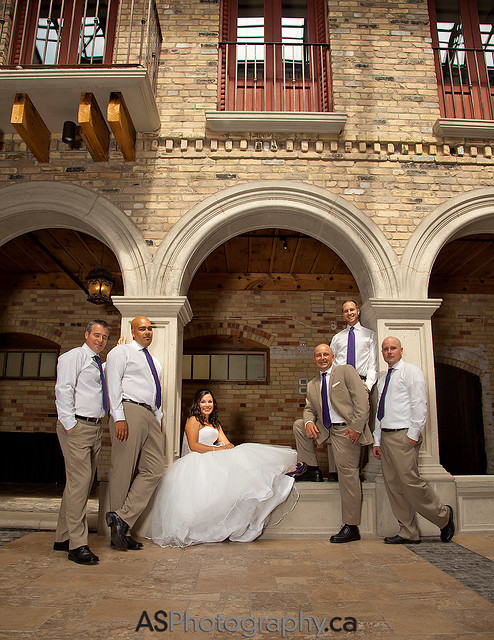 The groom and his men hanging out with the bride in the arches of Hacienda Sarria in Waterloo