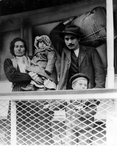 Immigrant family on a ship. Man holds their bundle of possessions on his back. by Kheel Center, Cornell University
