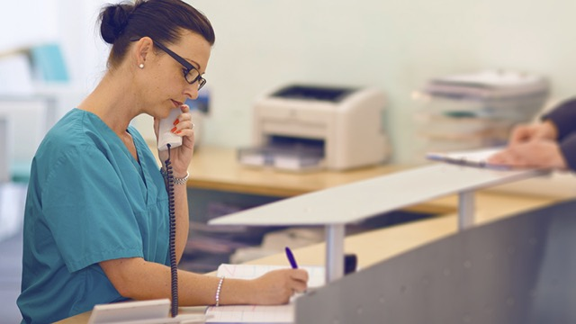 Medical receptionist at her desk, with someone filling out a form in the background