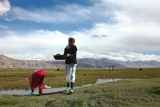 タシュクルガン、湿地帯で洗濯する少女たち