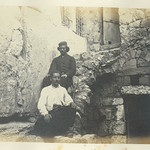 Two men sitting next to lintel of Barclay