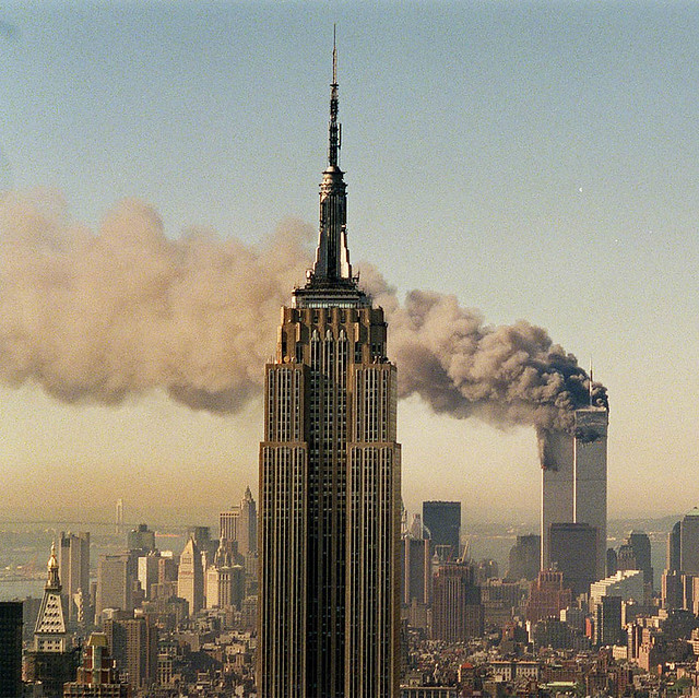 The Twin Towers of the World Trade Center burn behind the Empire State Buildiing in New York, by Marty Lederhandler