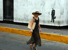 Stylish blonde business woman in a large straw hat, wearing a heavy gold link chain, silk dress, straw bag, guerrilla wall art of a business man with a brief case, Historical district, Mazatlan, Mexico