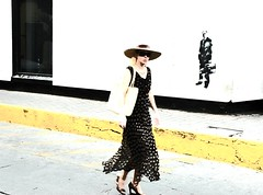 Simple: blonde Spanish woman tourist in a large straw hat, wearing a heavy gold link chain, silk dress, straw bag, guerrilla wall art of a business man with a brief case, Historical district, Mazatlan, Mexico