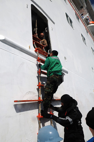 Sailor climbs aboard Carnival cruise ship from rigid hull boat. by Official U.S. Navy Imagery