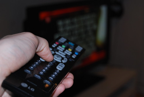 A television remote control being pointed at a television