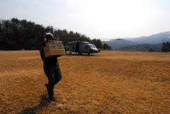 TAKIHANA, Japan (March 13, 2011) Naval Air Crewman 2nd Class Brian Fox, assigned to the Black Knights of Helicopter Anti-Submarine Squadron (HS) 4, carries supplies to Japanese aid workers. (U.S. Navy photo by Mass Communication Specialist 3rd Class Dylan McCord)
