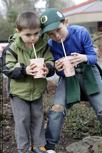 brothers enjoying strawberry milkshakes, halfway through a long walk