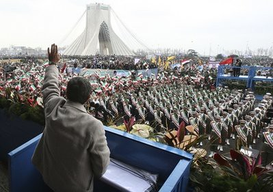 Iranian President Mahmoud Ahmadinejad, waves to the crowd in a rally marking the 32nd anniversary of the 1979 Islamic Revolution, at the Azadi (Freedom)Square, in Tehran, Iran, Friday, Feb. 11, 2011, while the Azadi monument tower is seen in background.  by Pan-African News Wire File Photos
