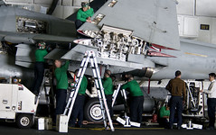 Sailors perform maintenance on EA-6B Prowler in hangar bay.