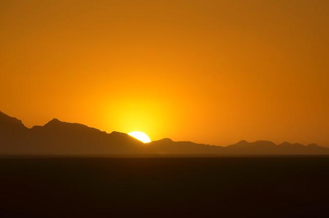 Puesta de sol en el desierto tras las montañas