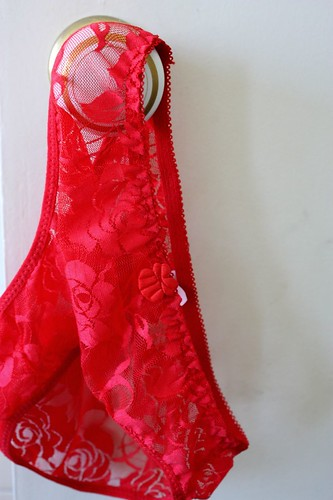 Red lacy underwear hanging on a doorknob