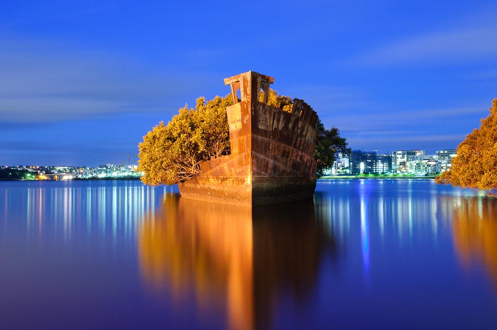 夜のシドニーの街と緑の廃船SS Ayrfield