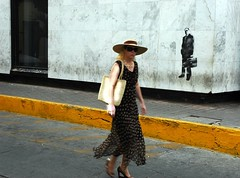 Bright similarity: Stylish blonde woman tourist in a large straw hat, wearing a heavy gold link chain, silk dress, straw bag, guerrilla wall art of a business man with a brief case, Historical district, Mazatlan, Mexico