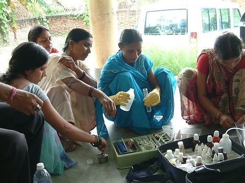 A group of rural women testing water quality using a field kit