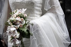 veil(0.0), groom(0.0), bride(1.0), bridal clothing(1.0), bridal veil(1.0), flower arranging(1.0), flower(1.0), gown(1.0), white(1.0), wedding(1.0), floral design(1.0), woman(1.0), female(1.0), flower bouquet(1.0), floristry(1.0), wedding dress(1.0), dress(1.0), ceremony(1.0),