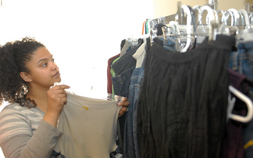 Young woman looks through clothes to sell.