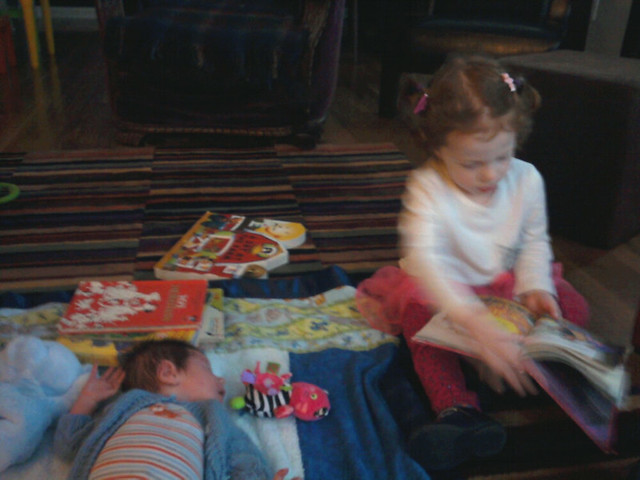 Reading to her baby brother.