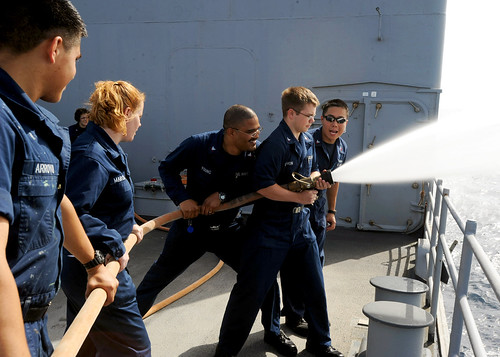 sailors manage a fire hose