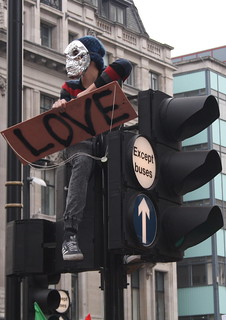 A protester sits on traffic lights outside Oxford Circus tube station