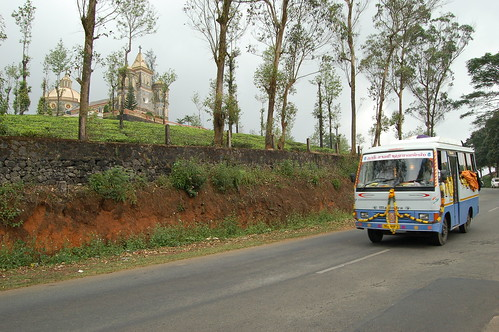 Eine Kirche in der Mitte einer Teeplantage, im Vordergrund ein Bus mit hinduistischen Pilgern.