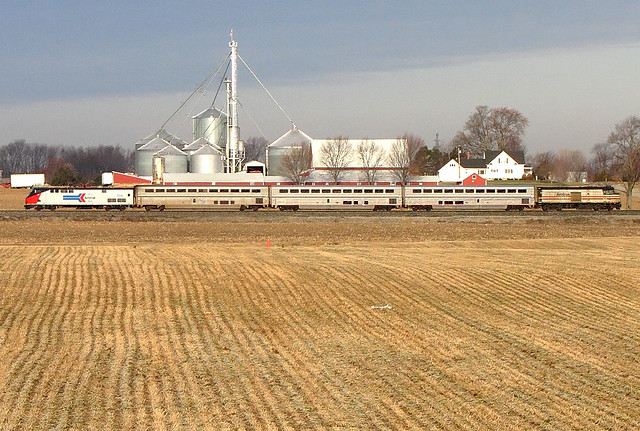An Amtrak train passing a farmhouse in Michigan