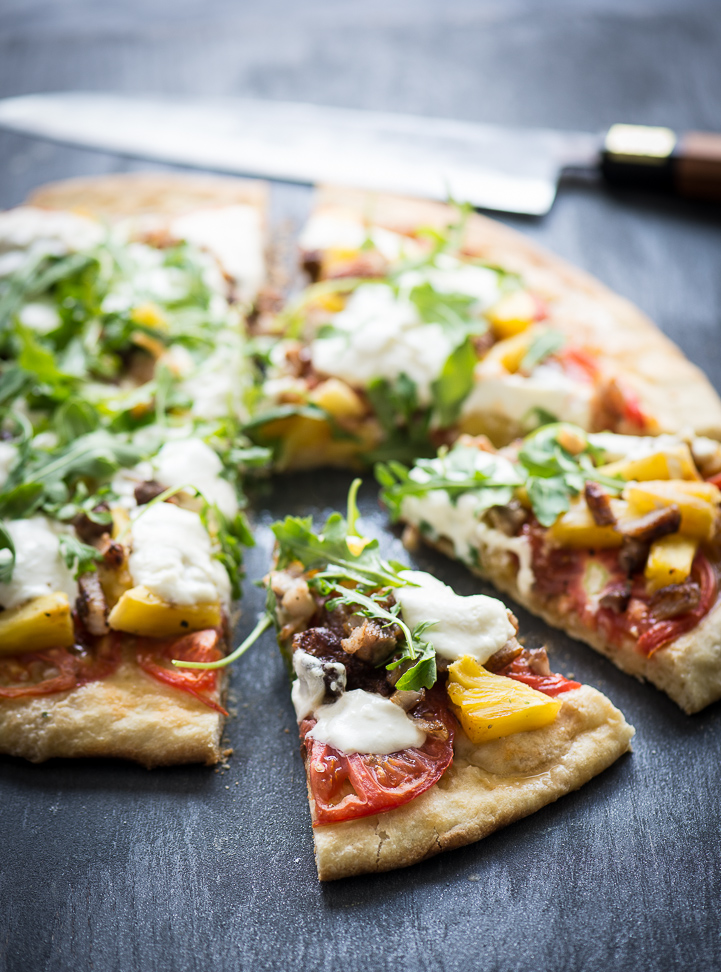 grilled pizza with pineapple, tomatoes, pork belly, white burrata cheese green arugula on a black background