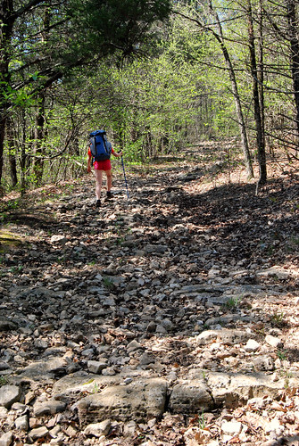 Picture showing a girl with a backpack hiking up a rocky hill trail in Piney Creek Wilderness in Missouri.