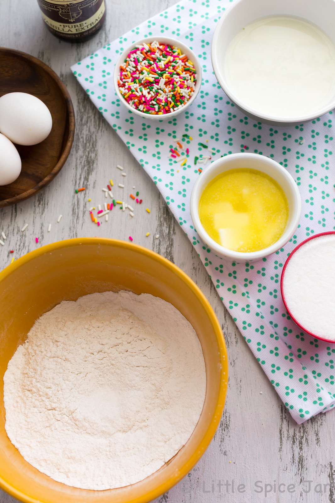 ingredients for funfetti cupcakes on white surface