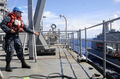 PACIFIC OCEAN (July 1, 2011) Ship's Serviceman Seaman Joshua Willard mans the phone distance line during the forward-deployed dock landing ship USS Germantown's (LSD 42) replenishment at sea (RAS) with USNS John Ericsson (T-AO-194). (U.S. Navy photo by Mass Communication Specialist 1st Class Johnie Hickmon)