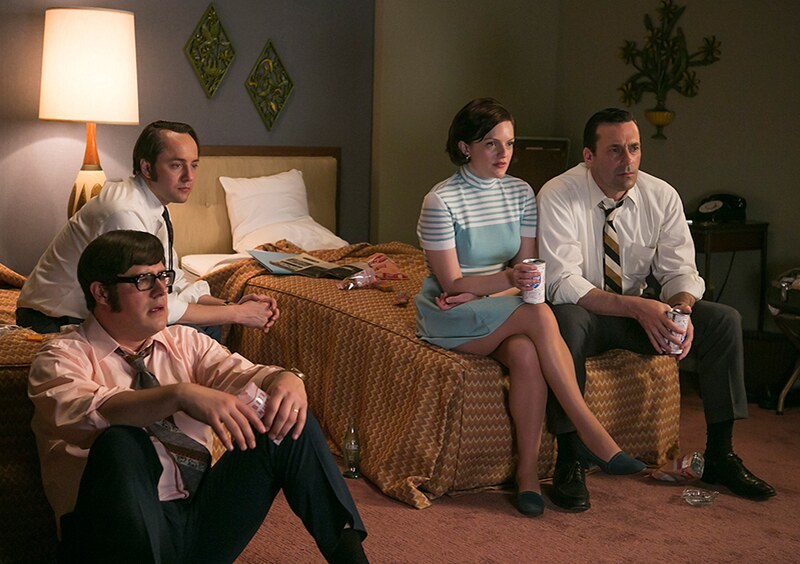 Harry, Pete, Peggy, and Don sit on hotel beds, watching the moon landing