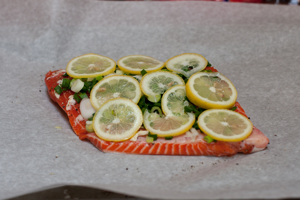 Salmon covered in scallions and lemons, with a bit of salt and pepper