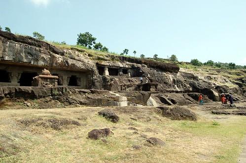 Eine Felsklippe in denen Eingänge zu Höhlen zu sehen sind. Die Eingänges sind richtig gross, wie durch die Besucher rechts am Bildrand zu sehen ist.