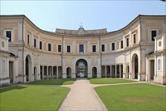 La cour de la villa Giulia et le bâtiment d'entrée avec le portique en hémicycle  La Villa Giulia a été édifiée dès 1551 à la demande du Pape Jules III (1550-1555) qui a fait appel à trois architectes éminents : Vasari, Vignole et Ammannati.   La villa est dotée d'une première cour intérieure avec un portique en hémicycle dont la voute est décorée à fresque. Les peintures murales imitent une tonnelle garnie de sarments de vigne, de rosiers et de jasmin.  En 1552, Bartolomeo Ammannati a réalisé un deuxième espace doté d'une loggia avec un escalier en fer à cheval, d'un nymphée avec rocailles, fausses grottes et cariatides, le tout décoré de  sculptures romaines. Les deux allégories fluviales représentent l'Arno et le Tibre.  Au 20ème siècle pour développer le musée national étrusque, créé initialement en 1889, deux ailes ont été ajoutées à la villa. Le temple étrusque d'Alatri a été reconstitué dans le jardin de droite.   Les photographies n'étant pas permises à l'intérieur du musée (on ne comprend pas pourquoi car il n'y a aucun problème de droit d'auteur et de risque de dégradations), on se contentera d'images du jardin et du bâti.   villagiulia.beniculturali.it/index.php?it/94/la-sede