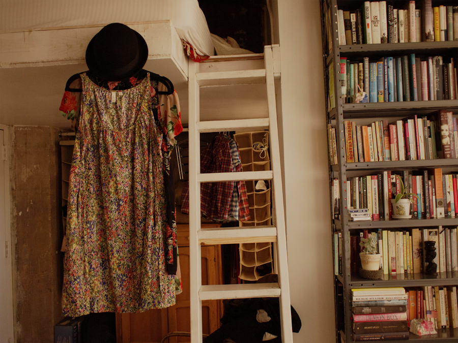 A bookcase, our loft-bed ladder, and my clothes and hat hanging from a hook.