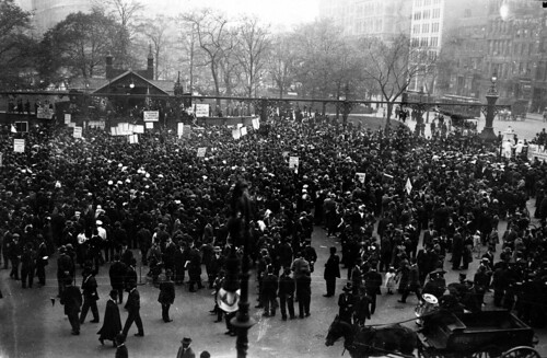 Striking garment workers rally in Union Square holding banners in Yiddish and English, 1913