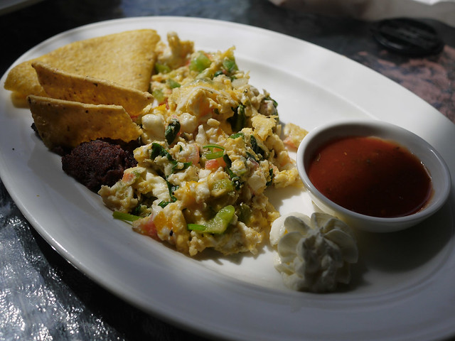 Spicy scrambled eggs served with refried beans and corn tortilla ...