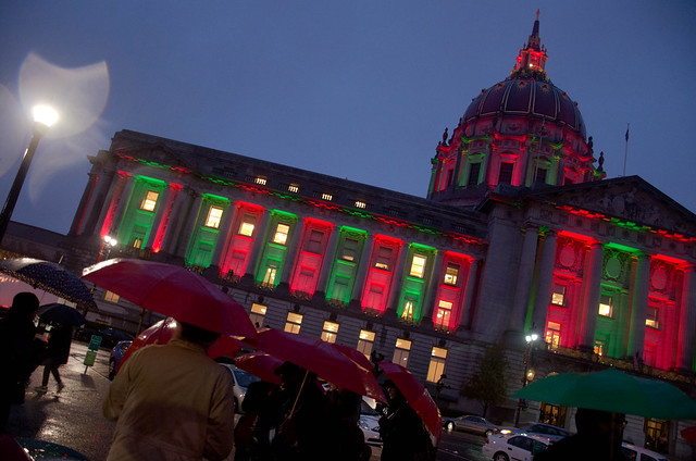 A civic building in SF is lit up red and green