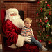 Kid sitting on Santa's Lap by fireplace and Christmas Tree