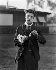 Buster Keaton picking flower petals, by John Springer