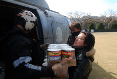 SUKUISO, Japan (March 18, 2011) Naval Air Crewman 2nd Class Joseph Conant, from Santee, Calif., gives a Japanese woman canned goods during a humanitarian assistance mission. (U.S. Navy photo by Mass Communication Specialist 3rd Class Dylan McCord/Released)