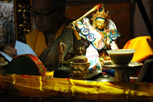 A statue of Manjushri wearing statue clothing,  His Holiness Dagchen Sakya on the throne reading a text,  religious items,  ...